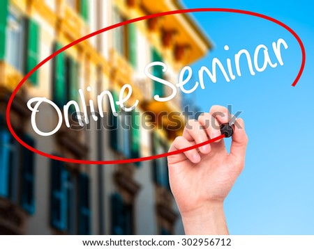 Man Hand writing Online Seminar with black marker on visual screen. Isolated on city. Business, technology, internet concept. Stock Photo - stock photo