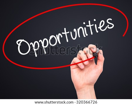 Man Hand writing Opportunities  with black marker on visual screen. Isolated on black. Business, technology, internet concept. - stock photo