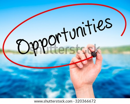 Man Hand writing Opportunities  with black marker on visual screen. Isolated on nature. Business, technology, internet concept. - stock photo