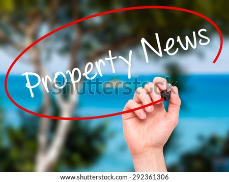 Man Hand writing Property News with black marker on visual screen. Isolated on nature. Business, technology, internet concept. Stock Image - stock photo