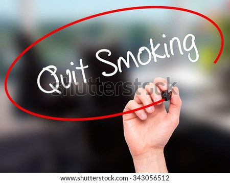 Man Hand writing Quit Smoking with black marker on visual screen. Isolated on office. Business, technology, internet concept. Stock Photo - stock photo