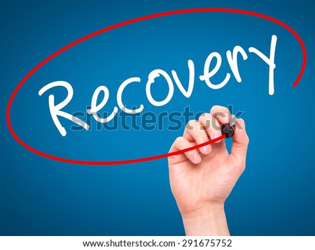 Man Hand writing  Recovery  with black marker on visual screen. Isolated on blue. Life, technology, internet concept. Stock Image - stock photo