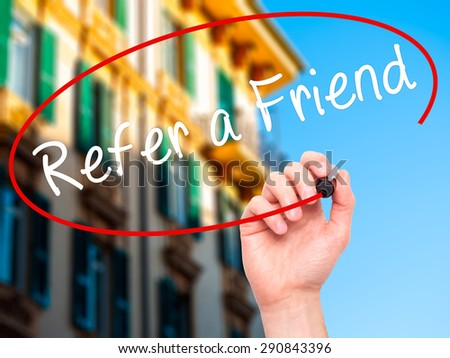 Man Hand writing Refer a Friend  with black marker on visual screen. Isolated on city. Business, technology, internet concept. Stock Image - stock photo
