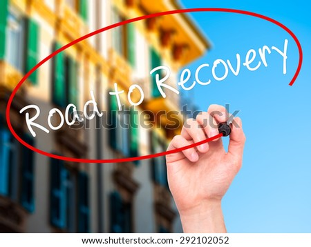 Man Hand writing Road to Recovery with black marker on visual screen. Isolated on city. Business, technology, internet concept. Stock Image - stock photo