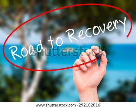Man Hand writing Road to Recovery with black marker on visual screen. Isolated on nature. Business, technology, internet concept. Stock Image - stock photo