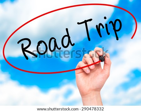 Man Hand writing Road Trip with black marker on visual screen. Isolated on sky. Travel, technology, internet concept. Stock Image - stock photo
