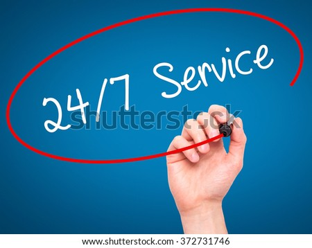 Man Hand writing 24/7 Service with black marker on visual screen. Isolated on background. Business, technology, internet concept. Stock Photo - stock photo