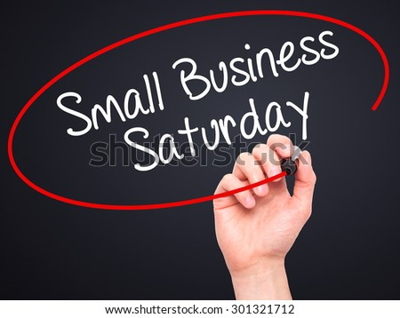 Man Hand writing Small Business Saturday with black marker on visual screen. Isolated on black. Business, technology, internet concept. Stock Photo