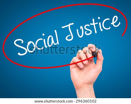 Man Hand writing Social Justice with black marker on visual screen. Isolated on blue. Business, technology, internet concept. Stock Photo - stock photo