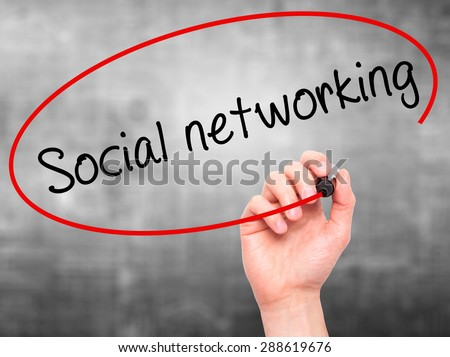 Man Hand writing Social networking with black marker on visual screen. Isolated on grey. Business, technology, internet concept. Stock Image - stock photo