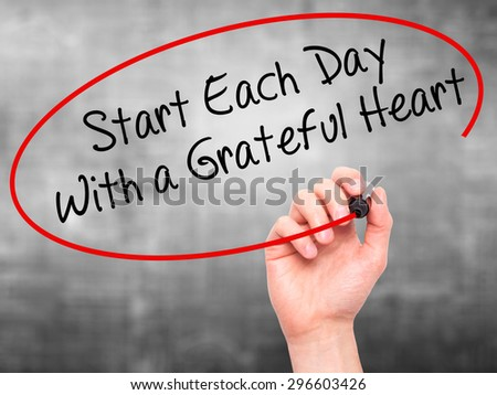 Man Hand writing Start Each Day With a Grateful Heart with black marker on visual screen. Isolated on grey. Business, technology, internet concept. Stock Photo