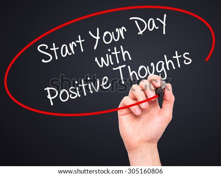 Man Hand writing Start your Dat with Positive Thoughts with black marker on visual screen. Isolated on black. Business, technology, internet concept. Stock Photo