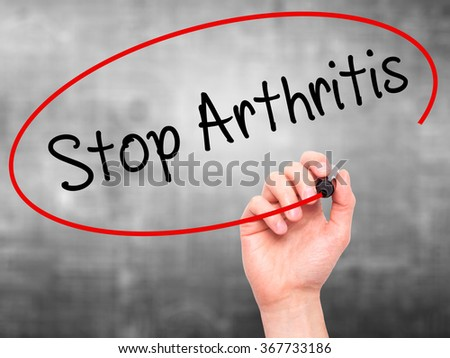 Man Hand writing Stop Arthritis with black marker on visual screen. Isolated on background. Business,  technology, internet concept. Stock Photo - stock photo