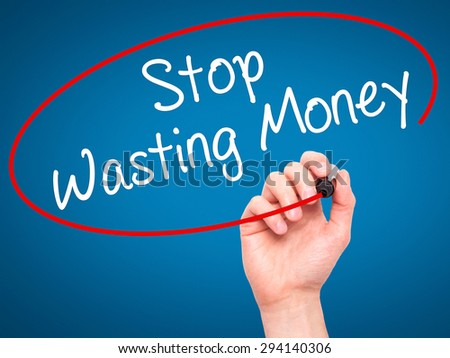 Man Hand writing Stop Wasting Money with black marker on visual screen. Isolated on blue. Business, technology, internet concept. Stock Photo - stock photo