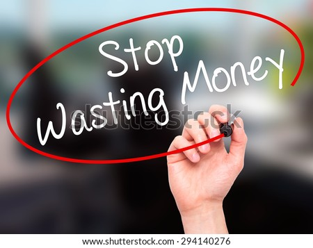 Man Hand writing Stop Wasting Money with black marker on visual screen. Isolated on office. Business, technology, internet concept. Stock Photo - stock photo