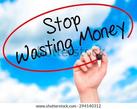 Man Hand writing Stop Wasting Money with black marker on visual screen. Isolated on sky. Business, technology, internet concept. Stock Photo - stock photo