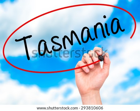 Man Hand writing Tasmania with black marker on visual screen. Isolated on sky. Business, technology, internet concept. Stock Photo - stock photo