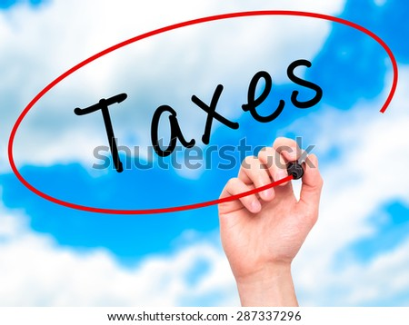 Man Hand writing Taxes with marker on transparent wipe board. Isolated on sky. Business, internet, technology concept. Stock Photo - stock photo