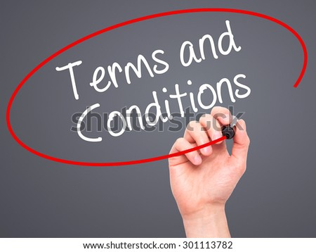 Man Hand writing Terms and Conditions with black marker on visual screen. Isolated on grey. Business, technology, internet concept. Stock Photo - stock photo
