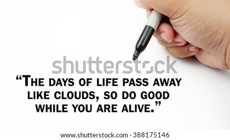 "Man Hand writing ""the days of life pass away like clouds, so do good while you are alive"" with black marker on visual screen. Isolated white background. Business, technology, internet concept."