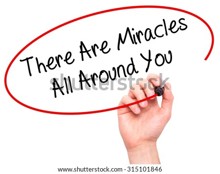Man Hand writing There Are Miracles All Around You  with black marker on visual screen. Isolated on white. Business, technology, internet concept. Stock Photo - stock photo