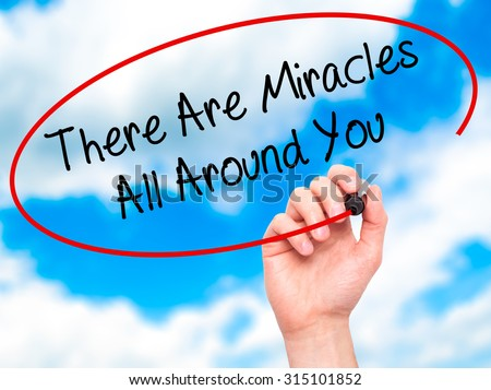 Man Hand writing There Are Miracles All Around You  with black marker on visual screen. Isolated on sky. Business, technology, internet concept. Stock Photo - stock photo