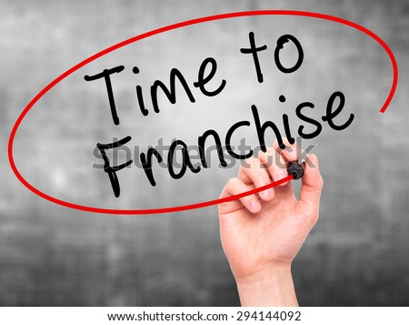 Man Hand writing Time to Franchise with black marker on visual screen. Isolated on grey. Business, technology, internet concept. Stock Photo - stock photo