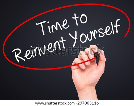 Man Hand writing Time to Reinvent Yourself with black marker on visual screen. Isolated on black. Business, technology, internet concept. Stock Photo