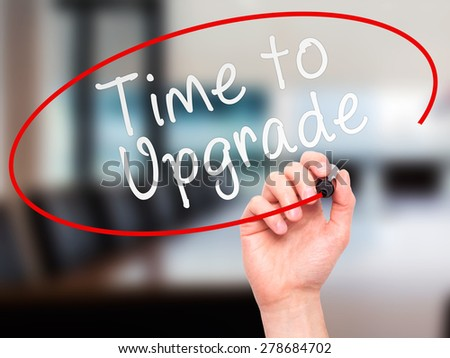 Man Hand writing Time to Upgrade with marker on transparent wipe board. Isolated on office. Business, internet, technology concept. Stock Photo - stock photo