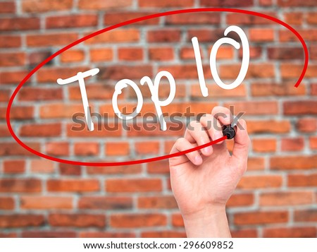 Man Hand writing Top 10 with black marker on visual screen. Isolated on bricks. Business, technology, internet concept. Stock Photo - stock photo