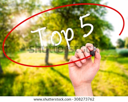 Man Hand writing Top 5 with black marker on visual screen. Isolated on nature. Business, technology, internet concept. Stock Photo - stock photo
