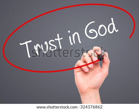 Man Hand writing Trust in God with black marker on visual screen. Isolated on grey. Business, technology, internet concept. Stock Photo - stock photo