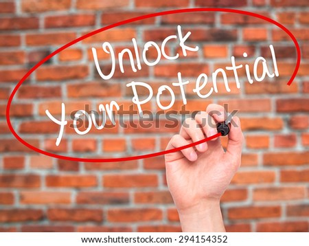 Man Hand writing Unlock Your Potential with black marker on visual screen. Isolated on bricks. Business, technology, internet concept. Stock Photo - stock photo