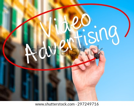 Man Hand writing Video Advertising with black marker on visual screen. Isolated on city. Business, technology, internet concept. Stock Photo - stock photo