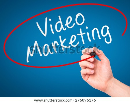 Man Hand writing Video Marketing black marker on visual screen. Isolated on blue. Business, technology, internet concept. Stock Image - stock photo