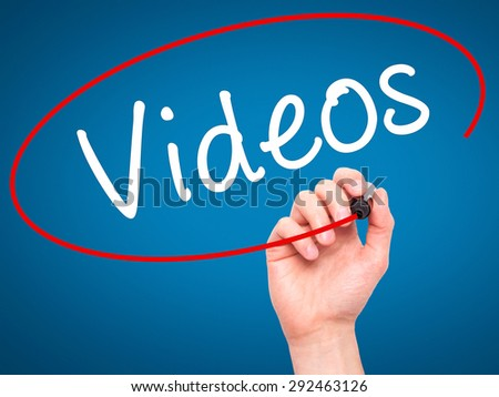 Man Hand writing Videos with black marker on visual screen. Isolated on blue. Business, technology, internet concept. Stock Image - stock photo