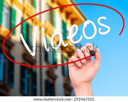 Man Hand writing Videos with black marker on visual screen. Isolated on city. Business, technology, internet concept. Stock Image - stock photo