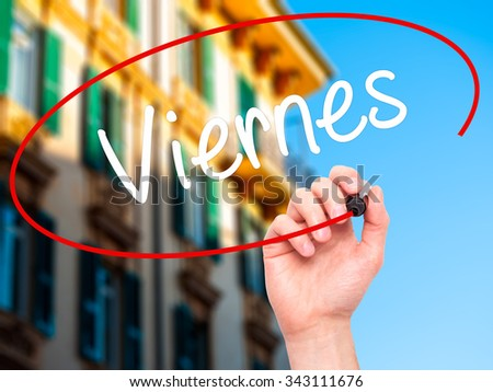 Man Hand writing Viernes (Friday in Spanish) with black marker on visual screen. Isolated on city. Business, technology, internet concept. Stock Photo - stock photo