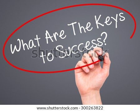 Man Hand writing What Are The Keys to Success? with black marker on visual screen. Isolated on grey. Business, technology, internet concept. Stock Photo