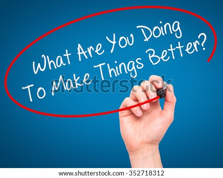 Man Hand writing What Are You Doing To Make Things Better? with black marker on visual screen. Isolated on background. Business, technology, internet concept. Stock Photo