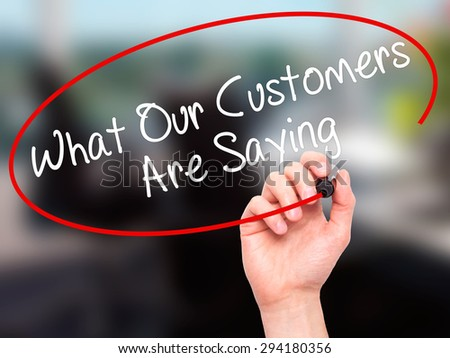 Man Hand writing What Our Customers Are Saying with black marker on visual screen. Isolated on office. Business, technology, internet concept. Stock Photo - stock photo