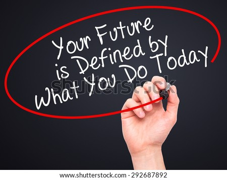Man Hand writing Your Future is Defined by What You Do Today with black marker on visual screen. Isolated on black. Business, technology, internet concept. Stock Image