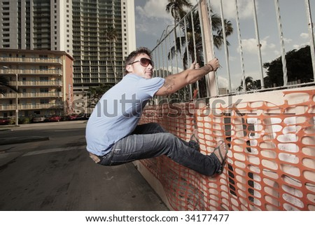 Man handing from a railing - stock photo