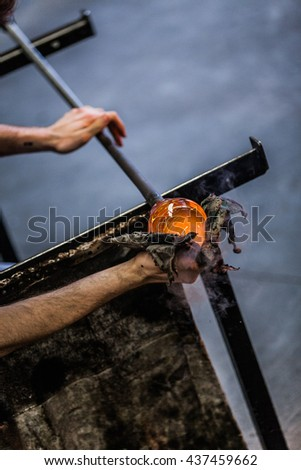 Man Hands Closeup Shaping a Blown Glass Piece with a Wet Newspaper - stock photo