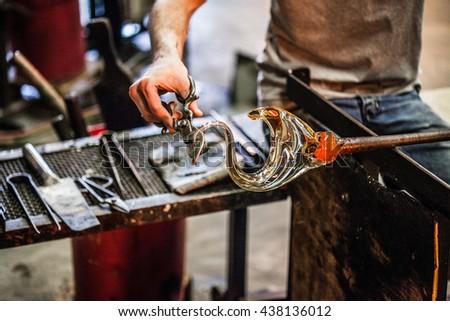 Man Hands Closeup Working on a Blown Glass Piece - stock photo