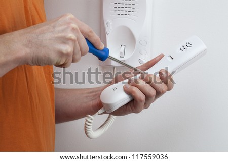 Man hands holding and repairing handset of entry phone - stock photo