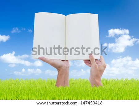 Man hands holding book on green grass with blue sky background