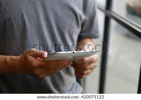 man hands holding digital tablet with empty blank screen for your text message, business person browsing internet or connecting to wireless via touchscreen pad sitting at brown wooden table - stock photo