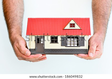 Man hands holds toy house isolated on white background with copy space.Concept photo of real estate business, home Insurance, house rental,buying, renting, mortgage, finance,service and repair costs - stock photo
