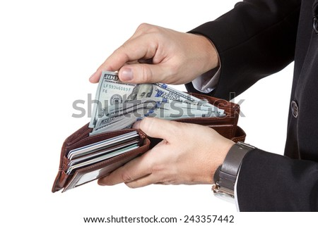Man hands in a suit with wristwatches gets money from her purse full of dollars and cards isolated on white background - stock photo